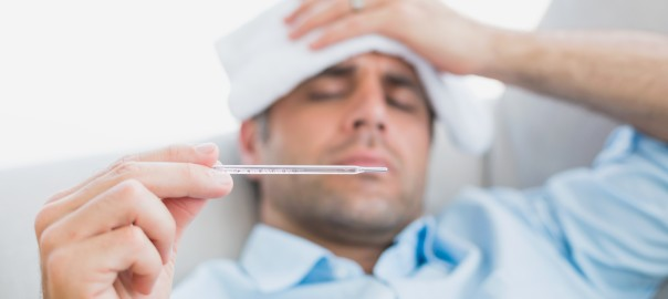 Sick man lying on sofa checking his temperature at home in the l