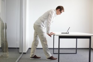 wrists exercise during office work - standing man reading at tab