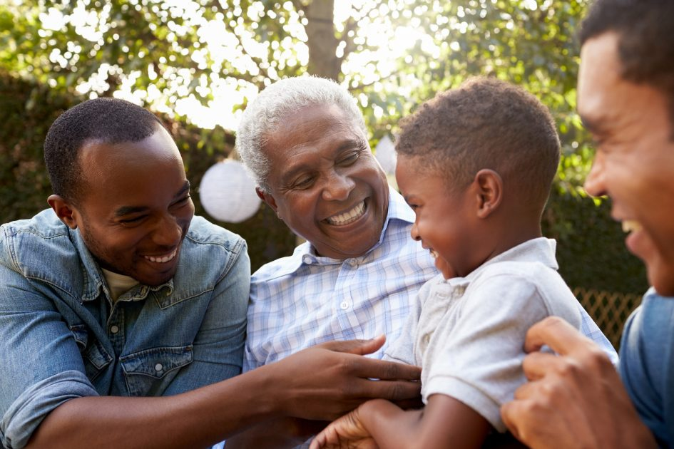 Black grandfather, sons and grandson talking in a garden