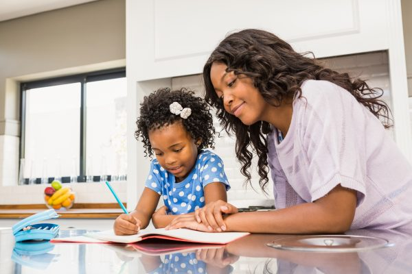 Young girl doing her homework with her mother